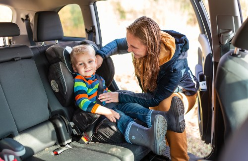 mom buckling young child into car seat