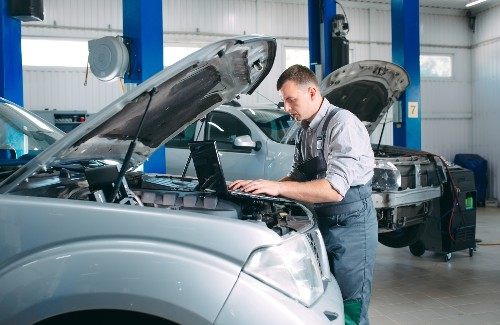 mechanic checking state of vehicle using laptop with hood upright