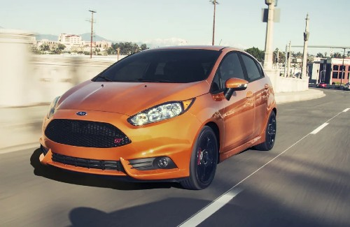orange 2019 Ford Fiesta front fascia driver side driving in a city
