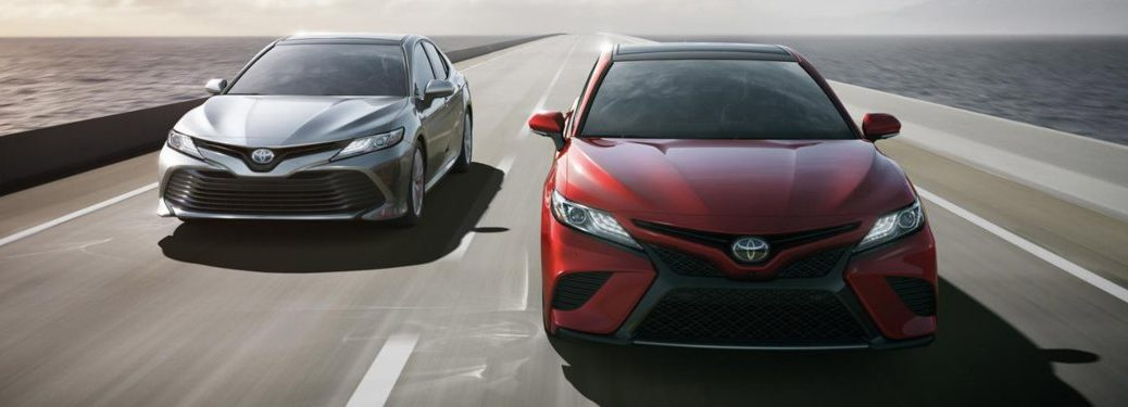 Two 2018 Toyota Camry models driving down a highway road