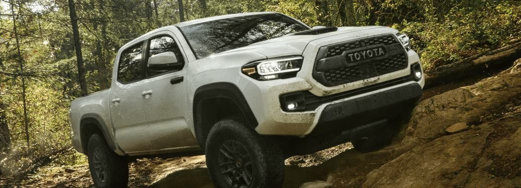 2021 Toyota Tacoma driving up an incline in the woods