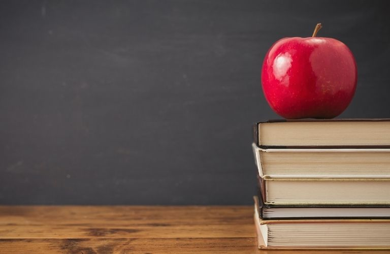 An apple placed on a stack of books