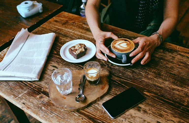 Image of a customer seated at a café with a coffee and brownies