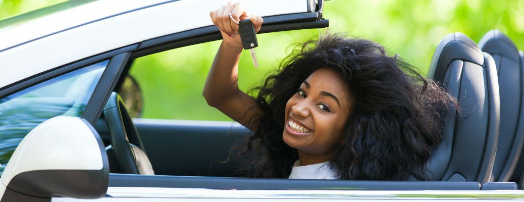 woman holding car key up in a convertible