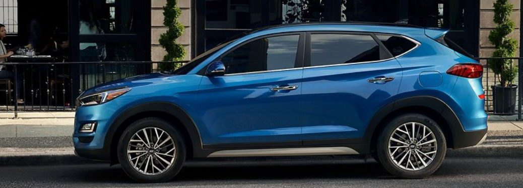 2021 Hyundai Tucson exterior driver side profile in front of cafe with plants