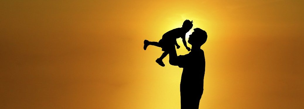 father holding up young child with sun in background