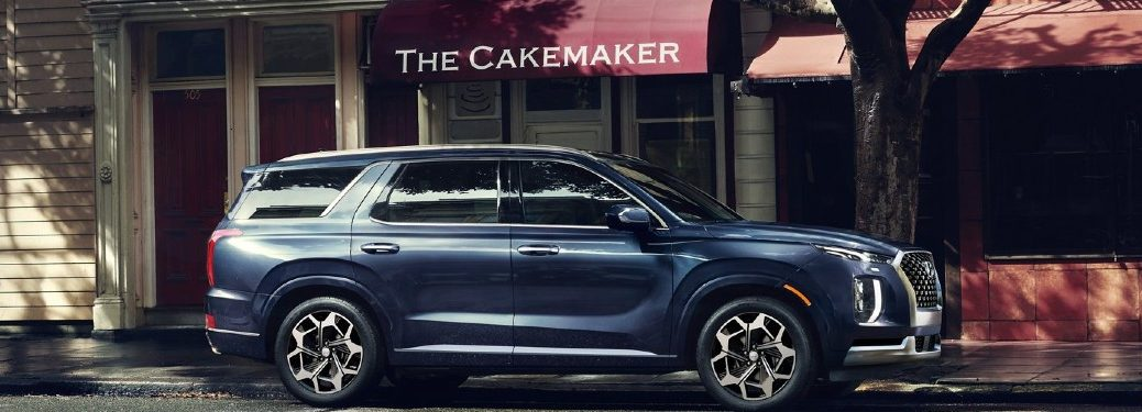 blue 2021 Hyundai Palisade passenger side parked on city street in front of cake shop