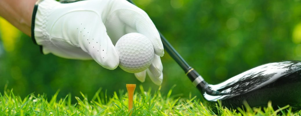 Golfer's hand holding golf ball with driver on green grass with golf course background