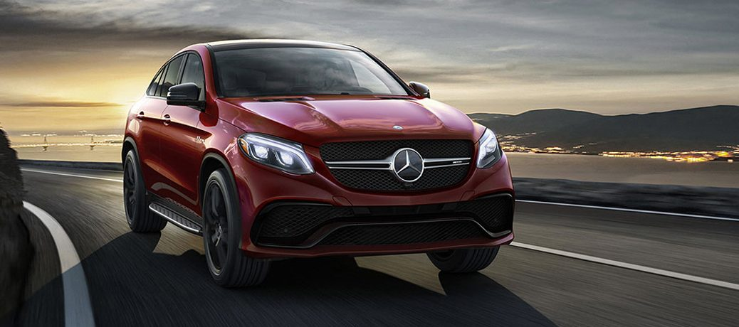 Red 2018 Mercedes-Benz GLE driving on the road with a sunset behind them