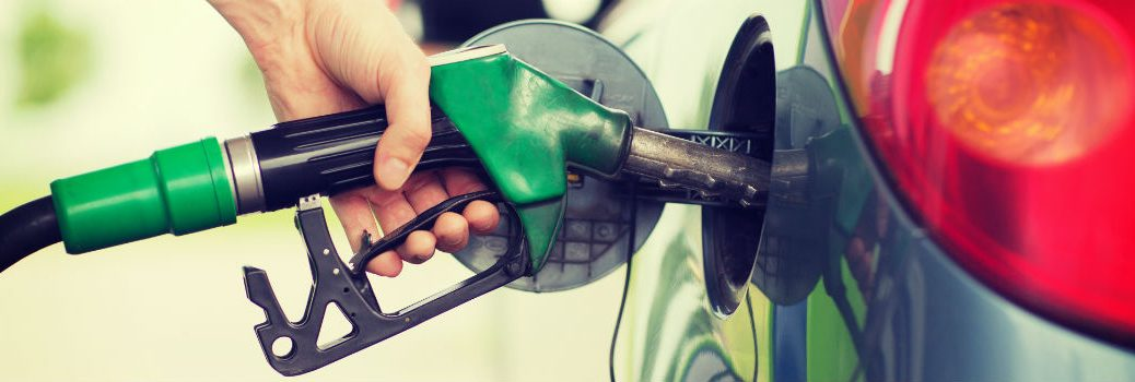 person filling vehicle with gasoline