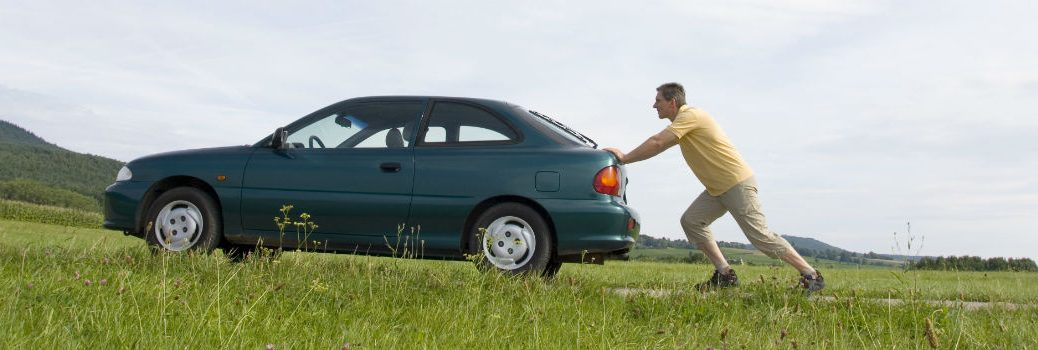 person pushing a car up a hill