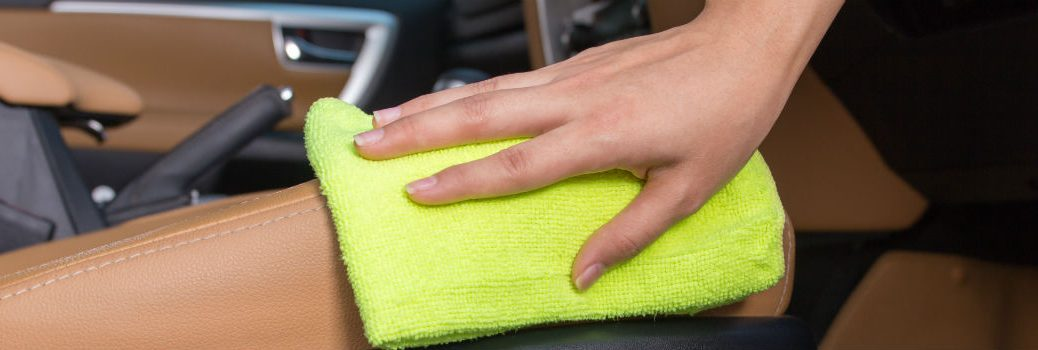 person scrubbing dashboard of vehicle with cloth