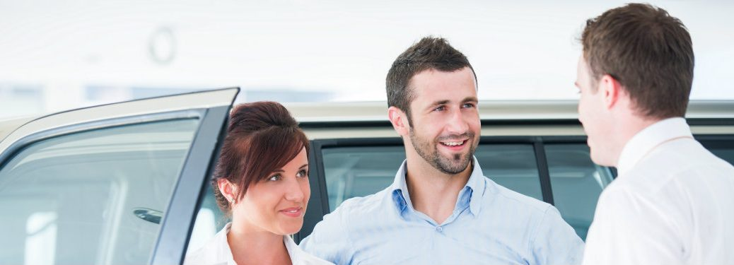 car salesman talking to young couple next to a car