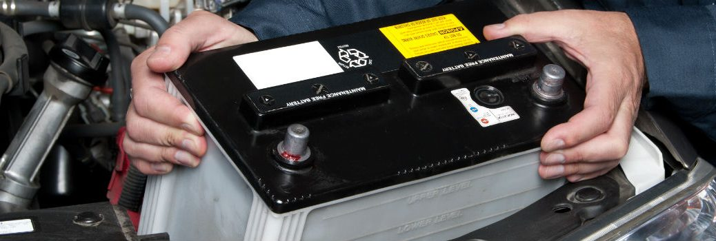 close-up look at car battery being held by person