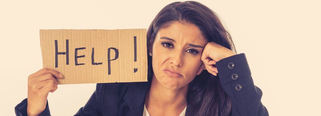 """Woman looks bummed and holds up a """"Help!"""" sign"""