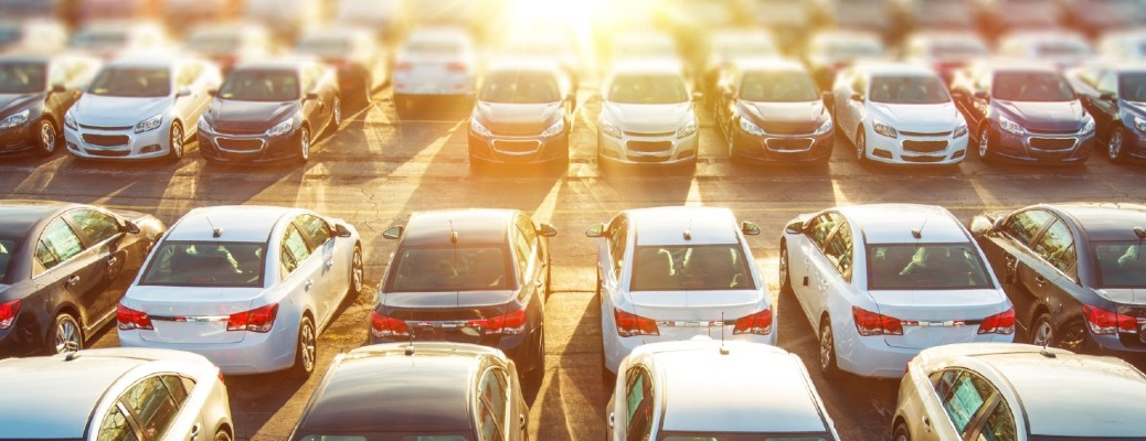 A variety of vehicles arrayed on a car lot under the sun