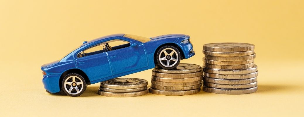 Image showing a toy car climbing a pile of coins