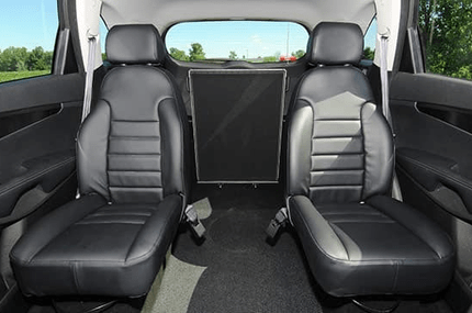 The wheelchair users sits between the center row bucket seats in the accessible Kia Sorento