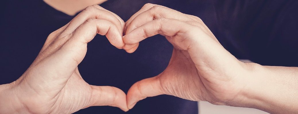 A stock photo of a person making a heart with their hands.