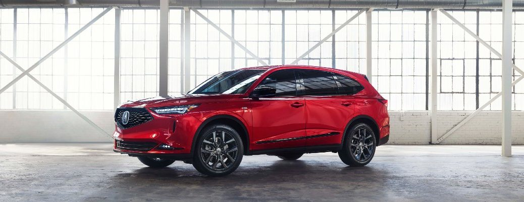 A left profile photo of the 2021 Acura MDX in an airplane hanger.
