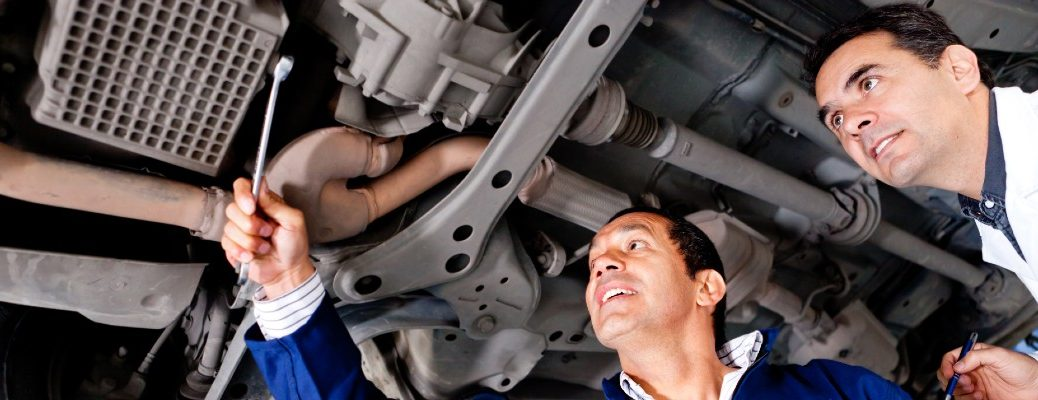 A stock photo of some people looking under a car at a repair shop.