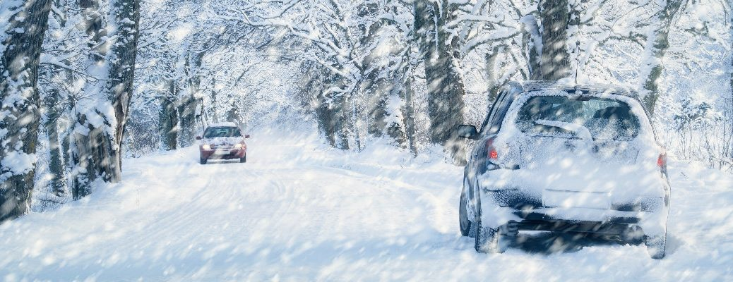 a heavy snowfall on a suburban road covering parked cars, trees, and the road during winter