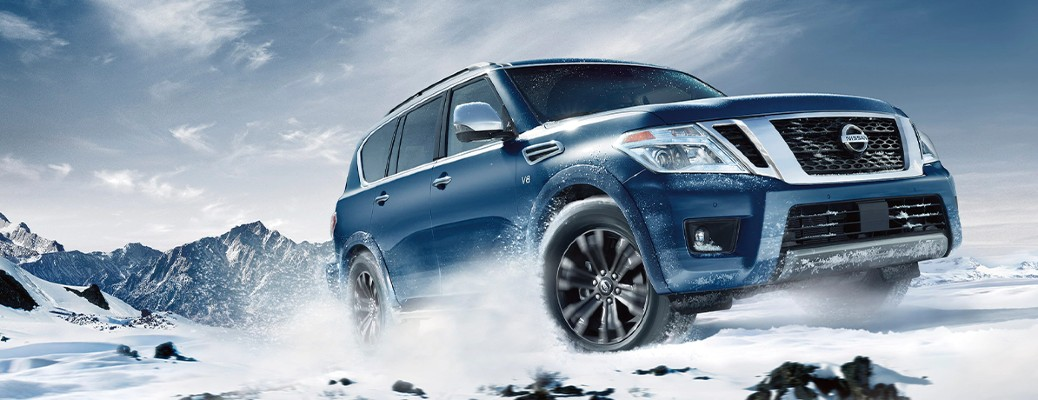 2020 Nissan Armada blue exterior front fascia passenger side driving on snow in mountain range