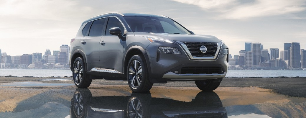 2021 Nissan Rogue parked on beach in puddle city skyline in background