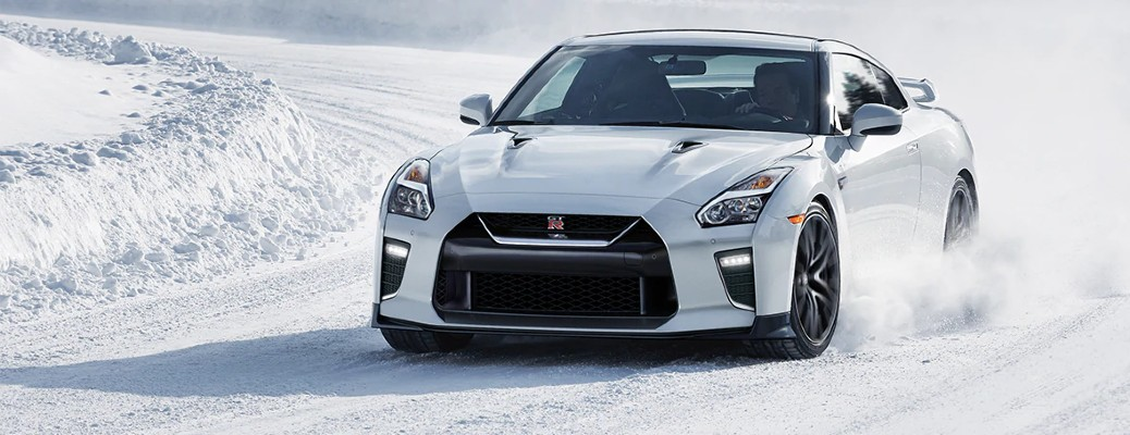 2021 Nissan GT-R Nismo white exterior front fascia driving on snow covered ground