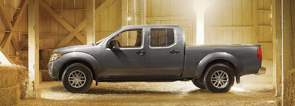2021 Nissan Frontier driver side parked in barn full of hay