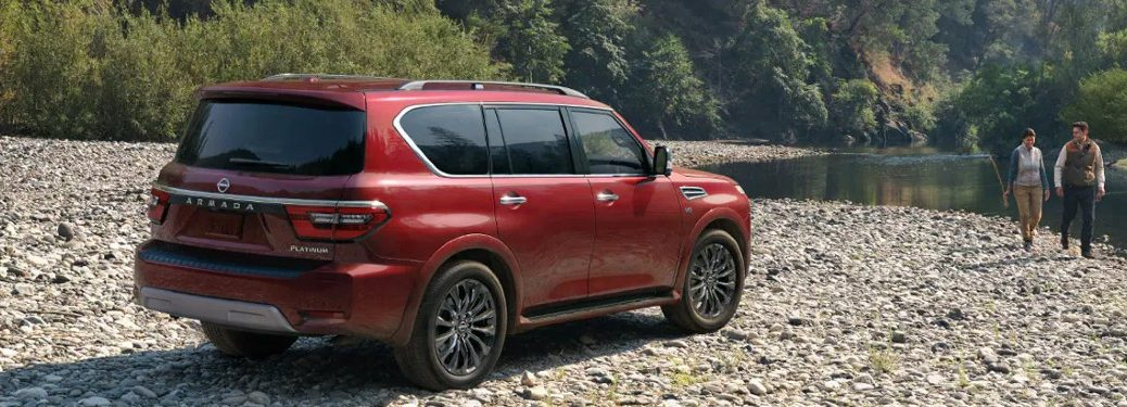 2021 Nissan Armada red exterior rear fascia passenger side parked on rocks near river