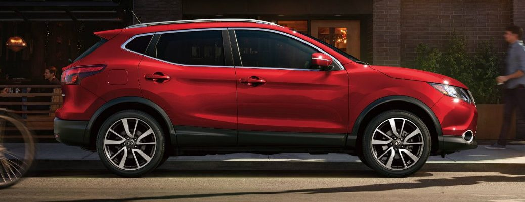 Profile view of red 2018.5 Nissan Rogue Sport parked in front of building on city street