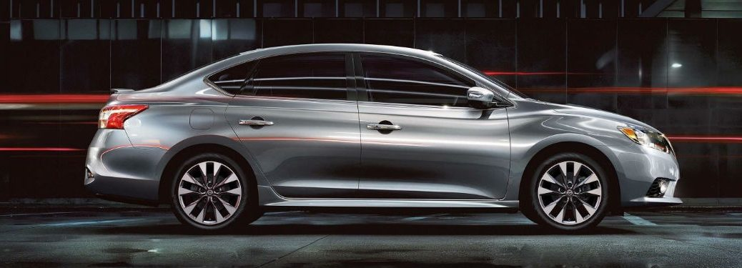 2018 Nissan Sentra vs 2018 Nissan Sentra NISMO with image of a Sentra driving on a dark road
