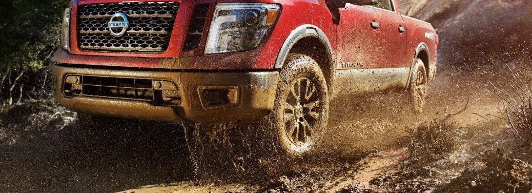 Which 2018 Nissan models have All-Wheel Drive? with image of a 2018 Nissan Titan driving through mud