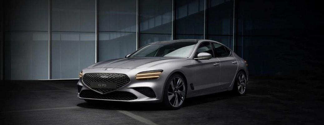 The silver Genesis G70 parked in front of a building.