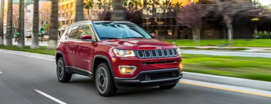 A 2021 Jeep Compass driving down a road with grass and trees in the background