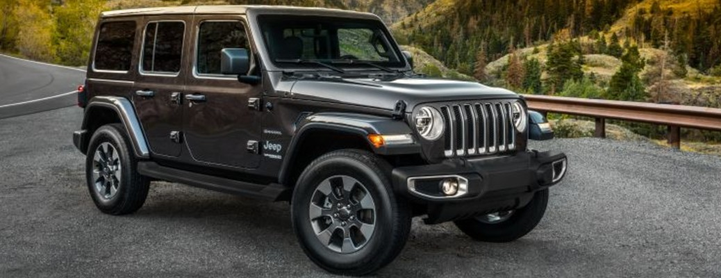 A black-colored 2021 Jeep Wrangler driving on a road