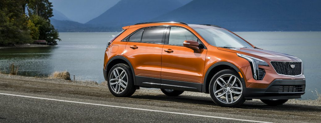 2019 Cadillac XT4 exterior side shot with orange paint color parked next to a lake with mountains, a forest, and clouds near it