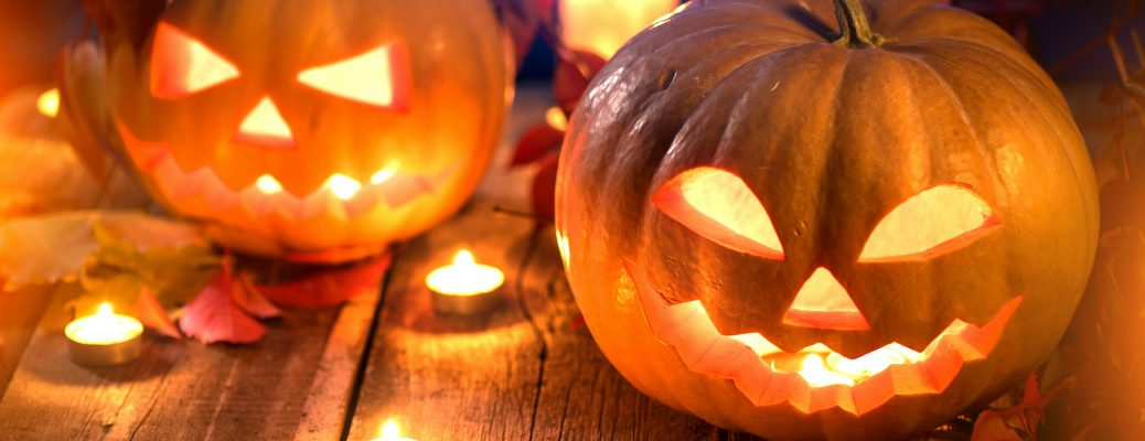 carved and lit jack o' lantern pumkins on a wooden table surrounded by leaves and candles