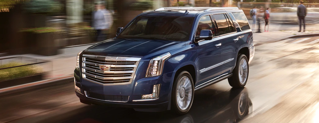 2019 Cadillac Escalade Dark Adriatic Blue Metallic paint color exterior shot driving around rainy streets with blurred pedestrians in the background