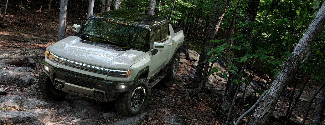 2022 GMC Hummer EV supertruck model exterior shot parked in the middle of a forest on a rocky hill