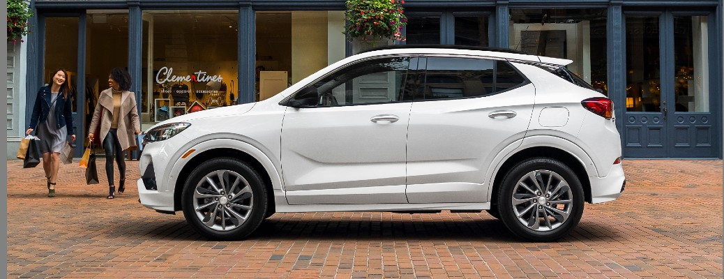 2021 Buick Encore GX Sport Touring exterior side shot with White Frost Tricoat paint color parked on a cobblestone road as a pair of ladies exit a shop