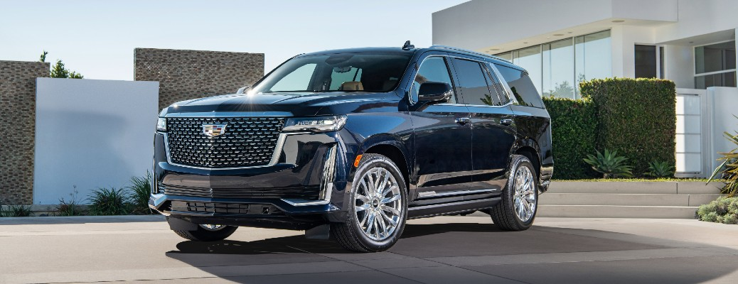 2021 Cadillac Escalade exterior shot parked on a driveway outside of a garage of a luxury home