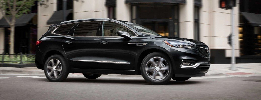 2021 Buick Enclave exterior shot with black paint color driving in a downtown area