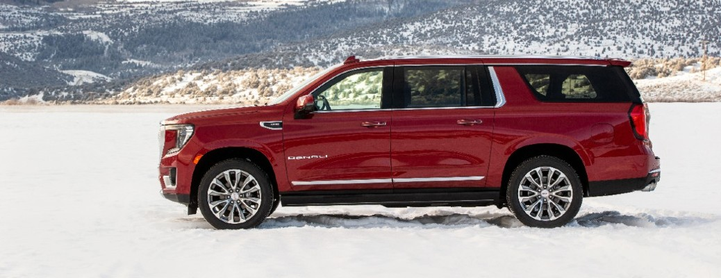 2021 GMC Yukon XL Denali exterior side shot with red paint color parked on a snowy field