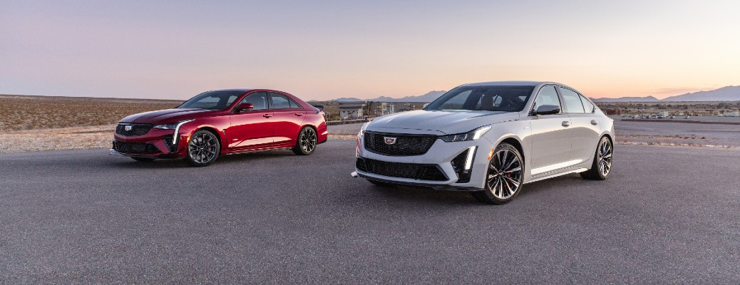 2022 Cadillac CT4-V Blackwing in red and 2022 Cadillac CT5-V Blackwing in white parked outside on an asphalt lot