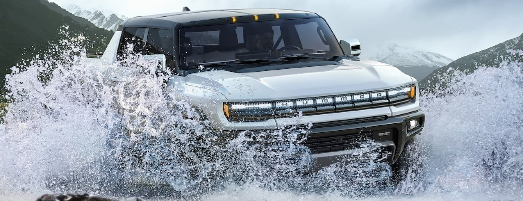 The front side of a white 2022 GMC Hummer EV driving through water.