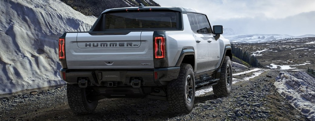 The rear view of a white 2022 GMC Hummer EV driving next to a snow bank.