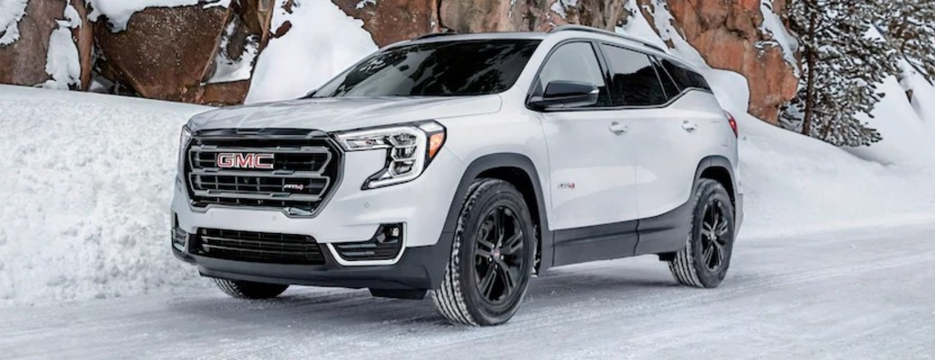 The front and side view of a white 2022 GMC Terrain in the snow.