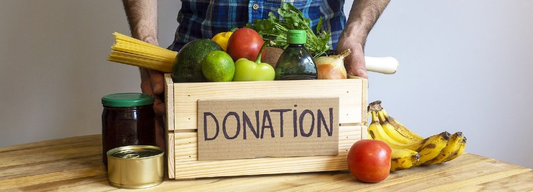 Man standing with food box donation in front of him
